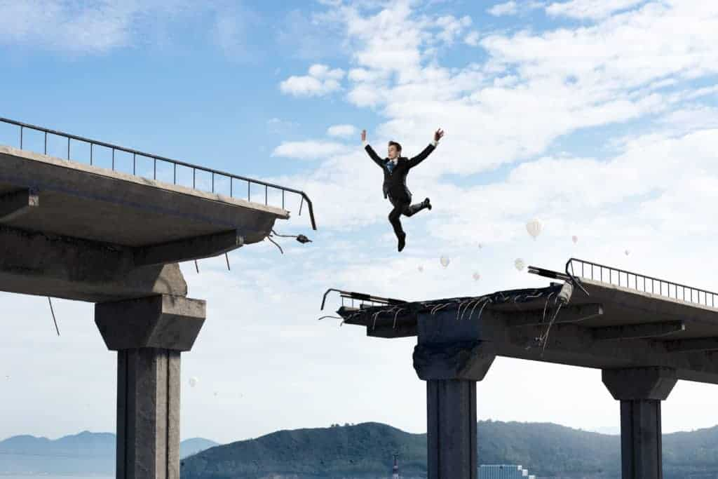 Businessman jumping over a gap in bridge as symbol of problem overcoming